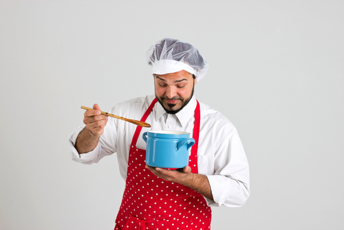 bearded chef in apron, tastes soup from blue pot with wooden spoon